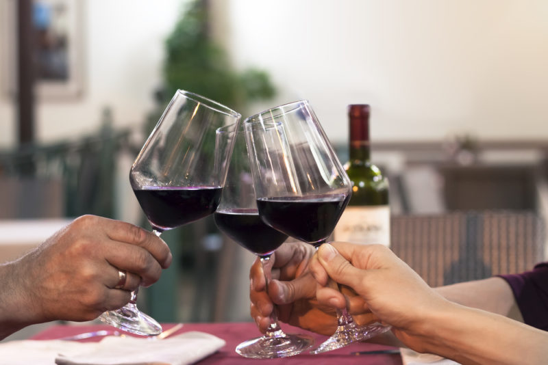 People sitting at a table toasting with glasses of red wine
