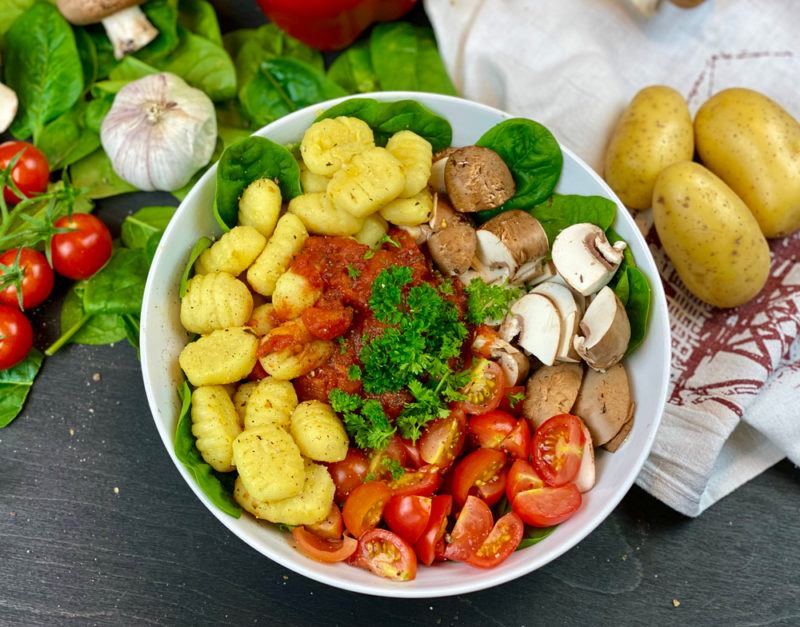 A white bowl that contains gnocci and various veggies