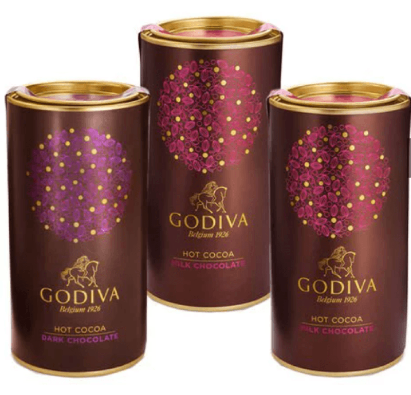 Three canisters of godiva hot chocolate, two are milk chocolate and the third is dark chocolate
