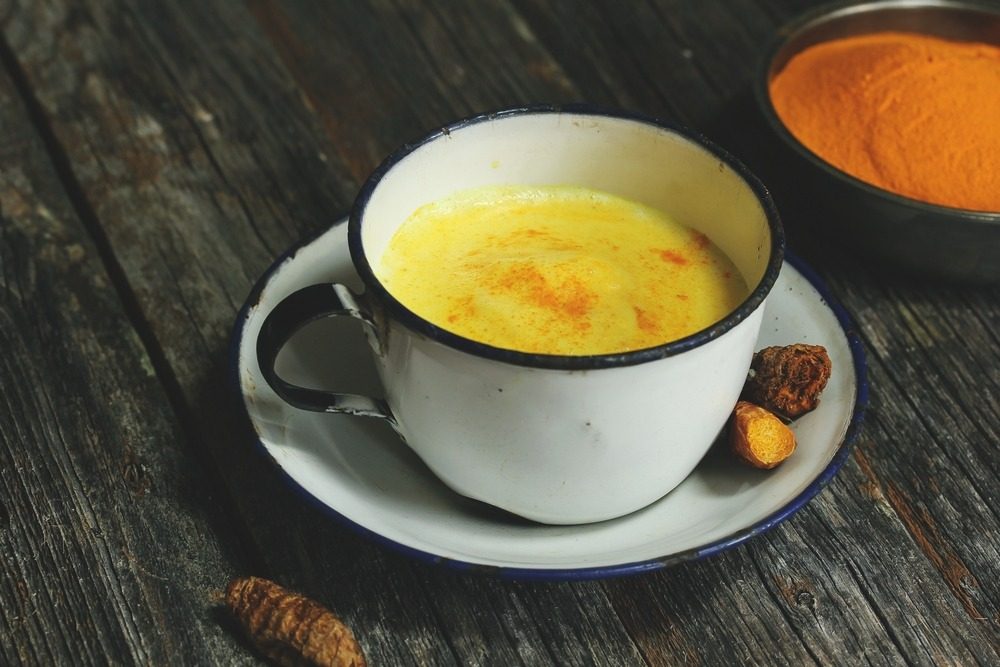 A white mug of golden milk with a black bowl of turmeric