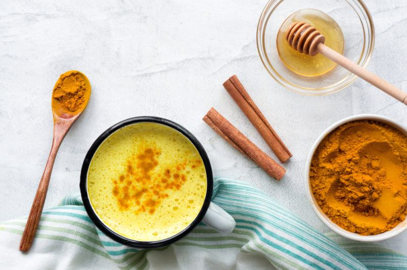 A mug of golden milk with turmeric, cinnamon and honey
