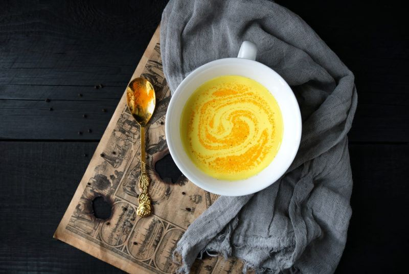 A mug of golden milk on a wooden board with a spoon and a cloth