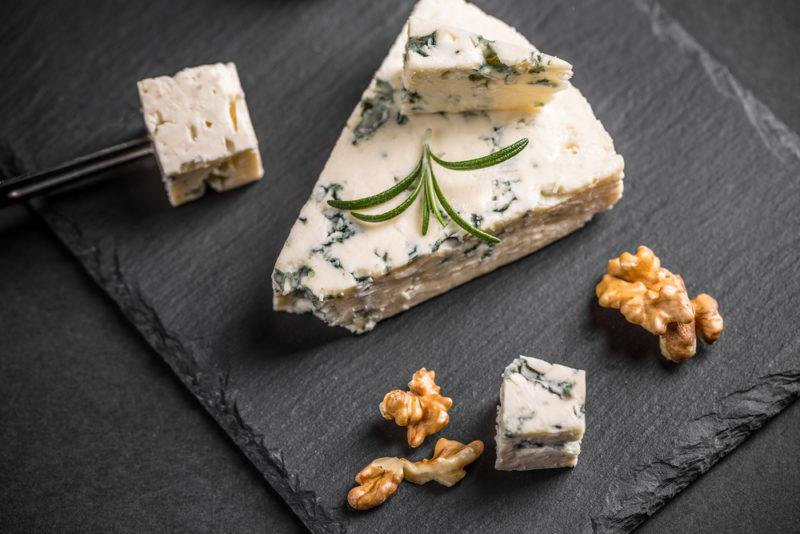 Gorgonzola cheese with walnuts on a black slate