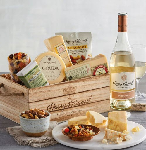A wooden grate with various cheeses, snacks and a bottle of wine.