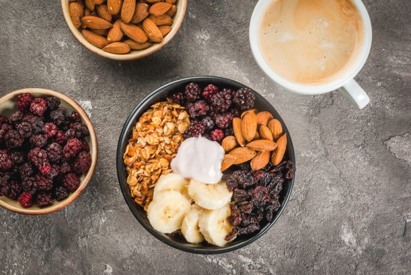 A black bowl with granola and a selection of toppings