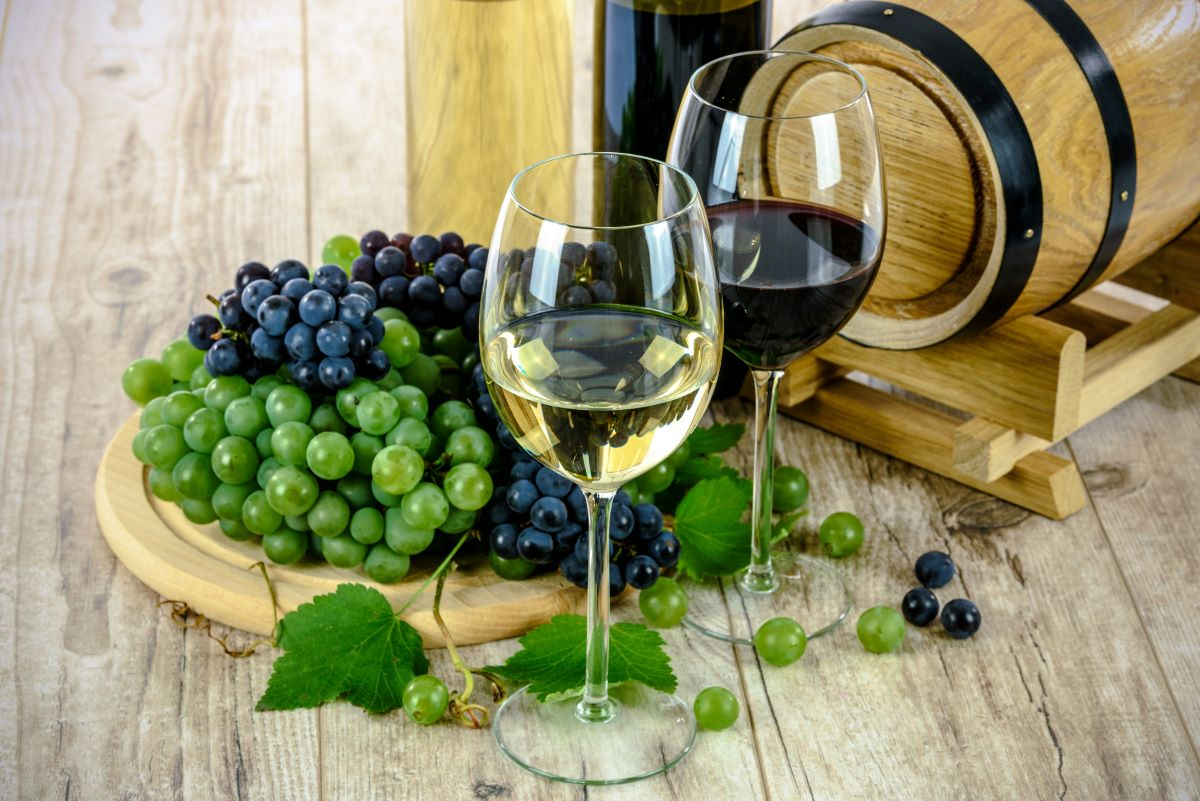Sweet Wine of the month clubs-two glasses of wine one red and one white, with a wooden round tray behind the glasses with grapes and a small wine barrel is in the background