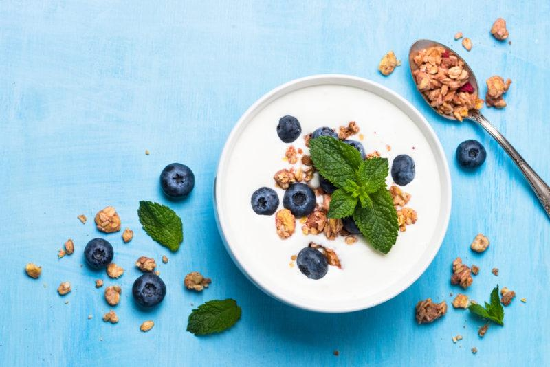 A bowl filled with Greek yogurt with granola and blueberries on top, against a blue background