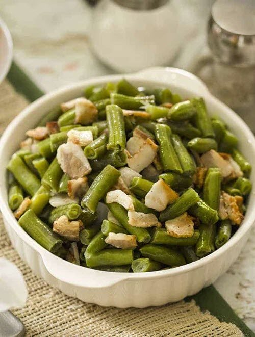 A bowl containing bacon and green beans