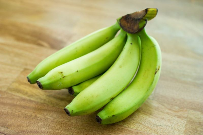 A bunch of green bananas on a light wooden table