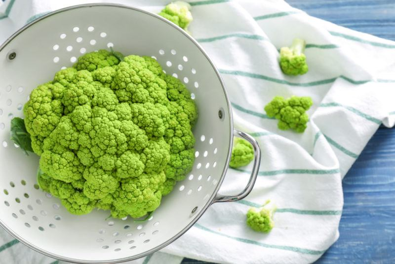 Green cauliflower in a colander with a tea towel underneath