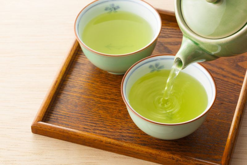 Green tea being poured into two mugs on a wooden board
