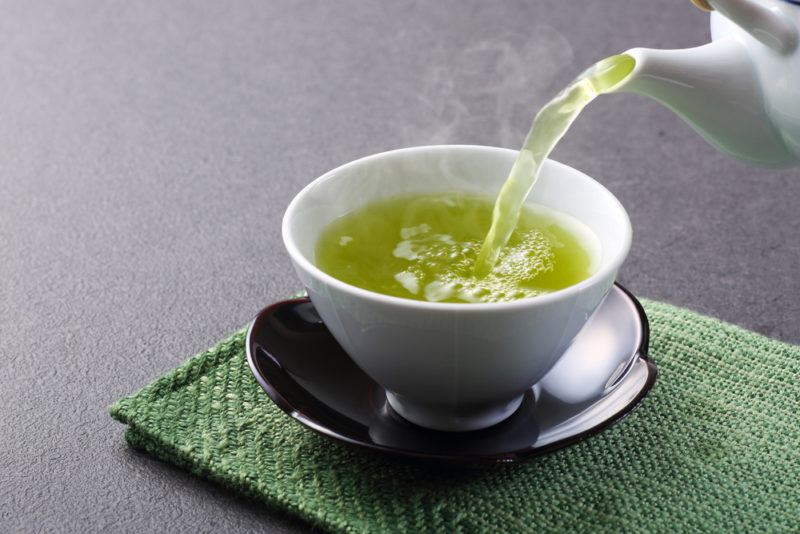 Green tea being poured into a small white bowl