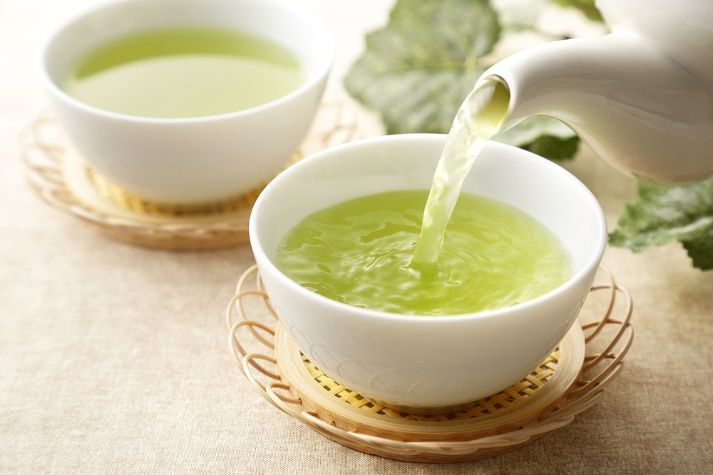 Two white bowls of green tea with tea being poured into them