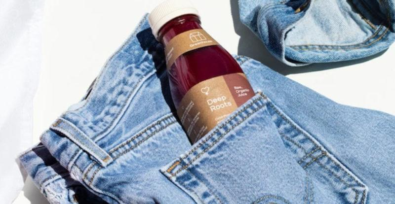 A Deep Roots bottle of juice from Greenhouse Juices in the pocket of a pair of jeans