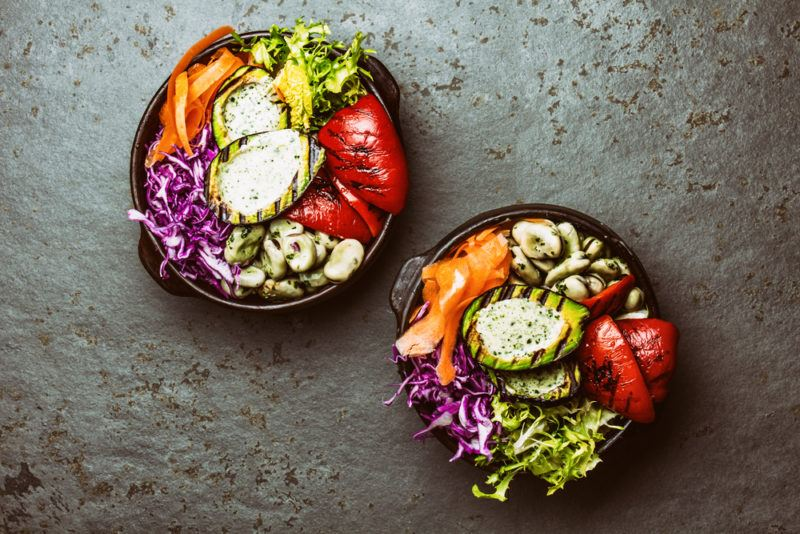 Two black bowls with healthy ingredients, including grilled stuffed avocados