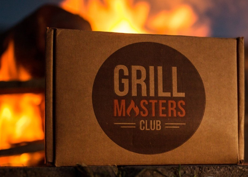 Cardboard Grill Masters Club box sitting on a tree stump.  Open bonfire in the background.  Box has a brown circle that stated Grill Masters Club in the Middle