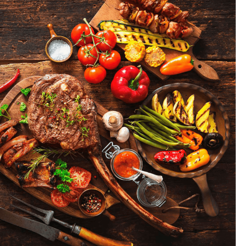 A rustic wooden table with different boards and wooden bowl displaying various grilled and fresh foods along with some sauces and salt and peppercorn.  Grilled vegetables, kabobs, steaks, and old-fashioned knife and meat fork in the lower left corner
