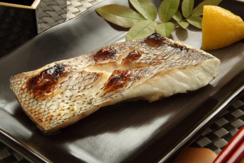 A black plate with grilled fish