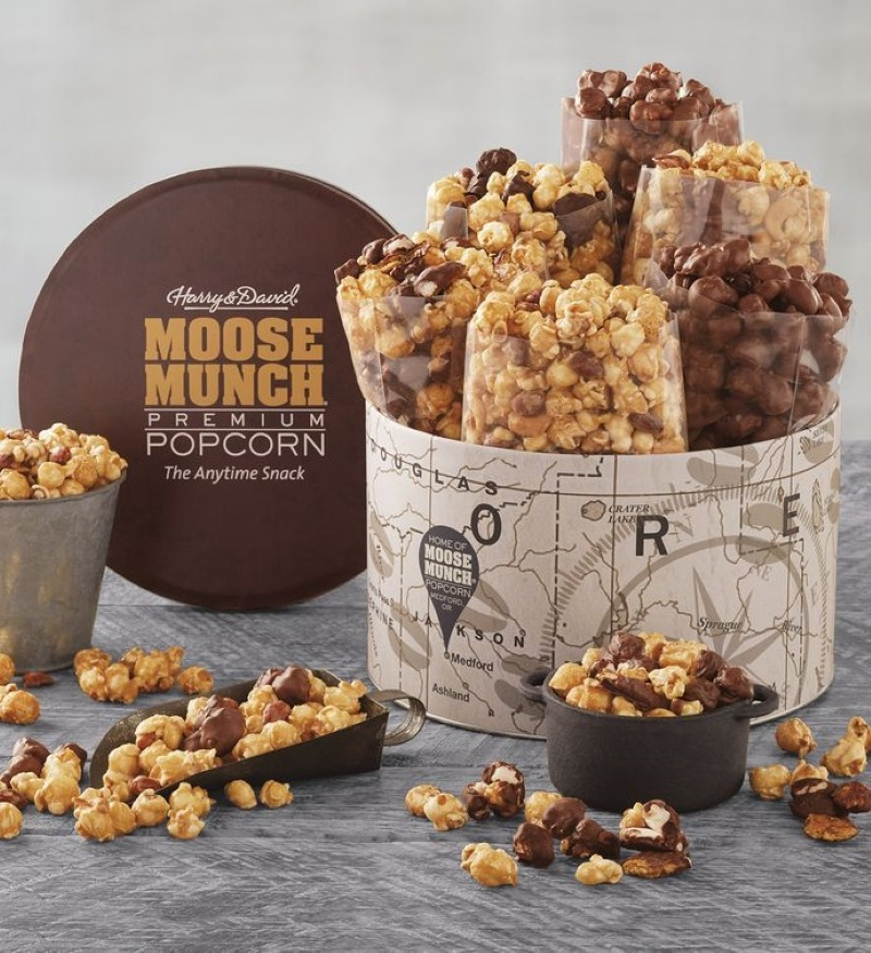 Variety of Moose Munch Popcorn displayed in a large tin featuring a map design, surrounded by an array of popcorn arranged decoratively around the tin.