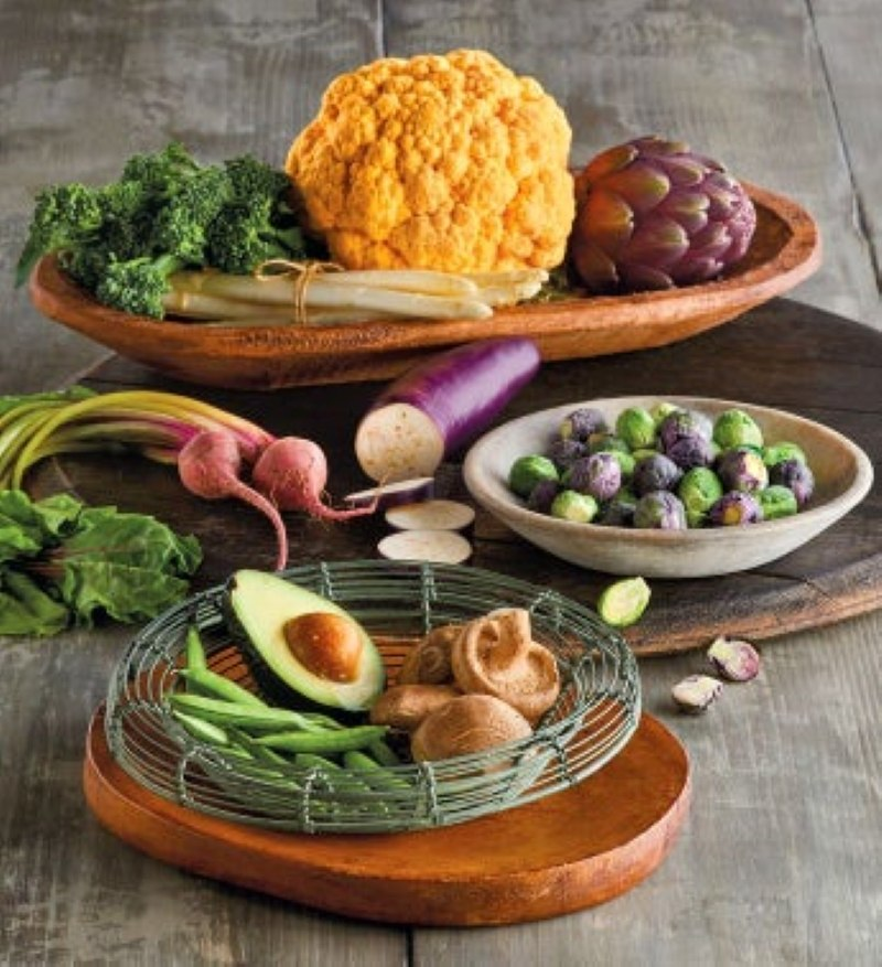 GRAY WOODEN TABLE WITH WOODEN BOWLS WITH COLORFUL VEGETABLES SUCH AS, ORANGE CAULIFLOWER, PURPLE ARTICHOKE, WHITE ASPARAGUS, AVOCADO, SHIITAKE MUSHROOM, GREEN AND PURPLE BRUSSELS SPROUTS, AND BEETS