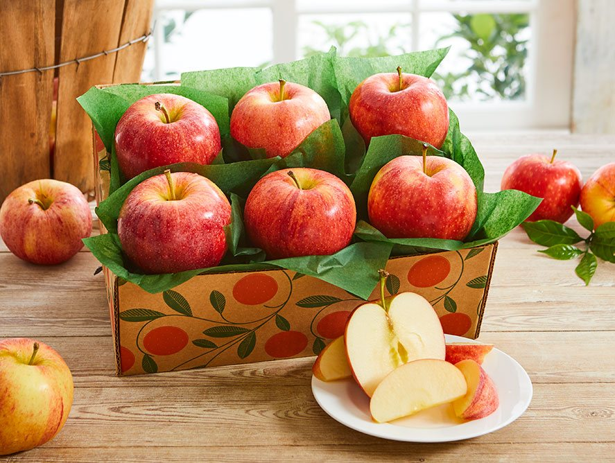 Decorative box with six red apples sitting in green tissue,  four apples on the outside of the scattered on wooden table, and one apple on a plate in lower right corner in front of the box sliced open.