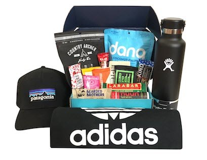 A black box with various snacks and an Adidas shirt