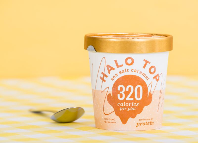 A pint of Halo Top ice cream next to a spoon
