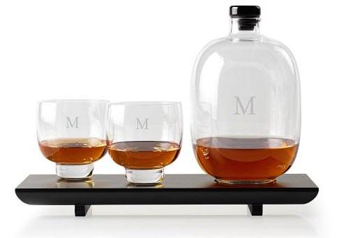 A wooden tray with an unusual monogrammed decanter and two glasses.
