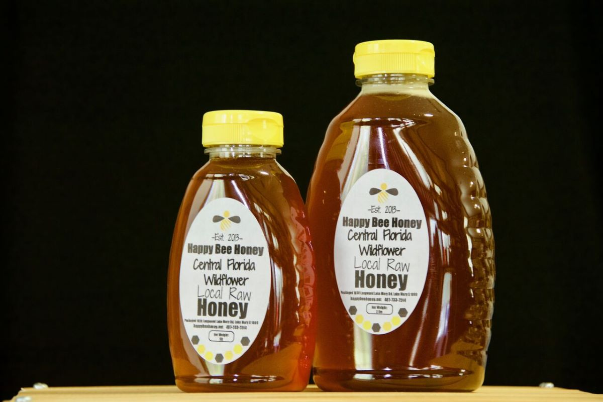 2 squeeze bottles with a yellow caps of happy bee honey