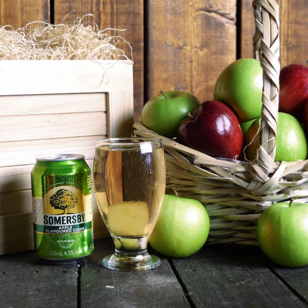 A can of Somersby cider next to a glass containing cider.  In the background is a basket of red and green apples and a crate