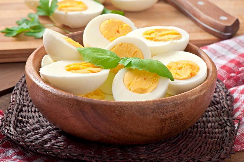 A wooden bowl containing hard boiled eggs