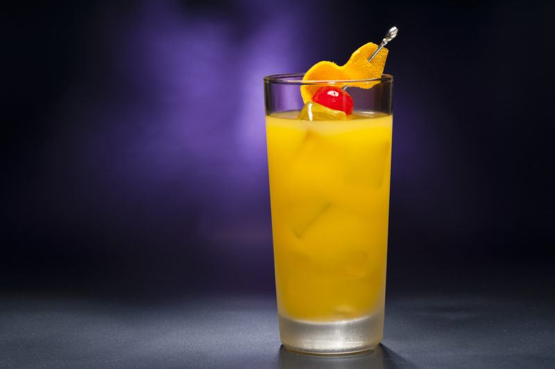 A tall Harvey Wallbanger cocktail against a purple background