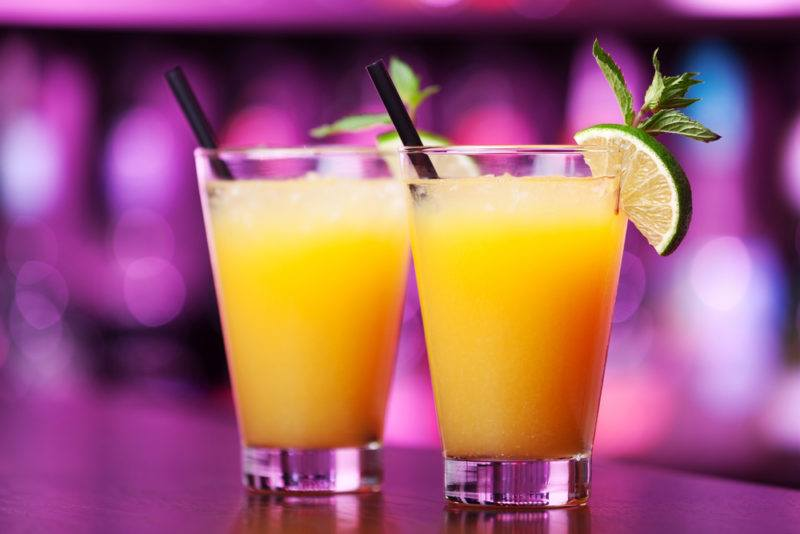 Two Harvey Wallbanger cocktails in front of an out-of-focus bar