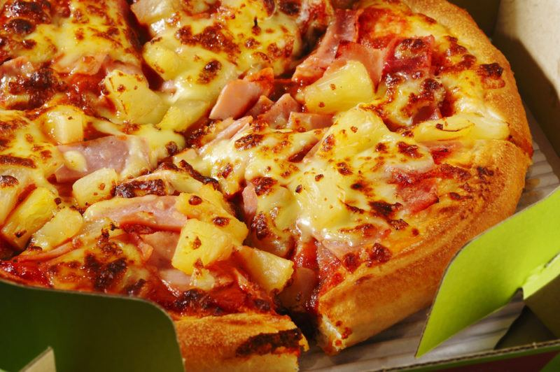 An Hawaiian pizza with ham and pineapple