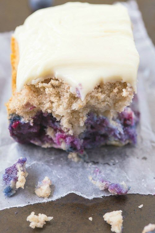 A blueberry cake with icing on parchment paper
