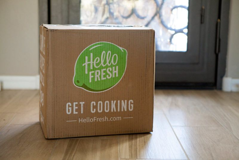 A Hello Fresh box in someone's entry way, showing the green Hello Fresh lime logo