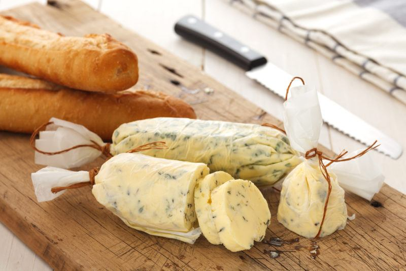 A wooden board with herbed butter, next to some bread sticks
