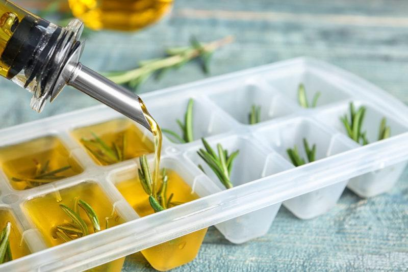 Adding olive oil and rosemary to an ice cube tray