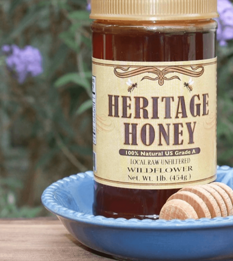 A jar of Heritage honey 100% natural US grade A local raw unfiltered wildflower.  Sitting in a blue bowl with a wooden honey dipper.  Sitting on a table outside