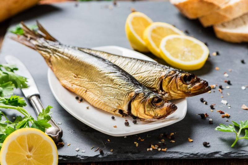 A white plate with two cooked herrings, with slices of lemon and cracked pepper on a table