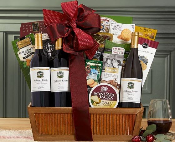 A wooden gift basket with a large selection of snacks and wine.