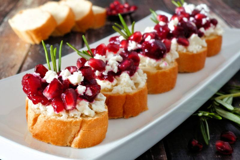 An oblong white plate with five pieces of crostini that have been topped with berries and cheese to make a holiday appetizer
