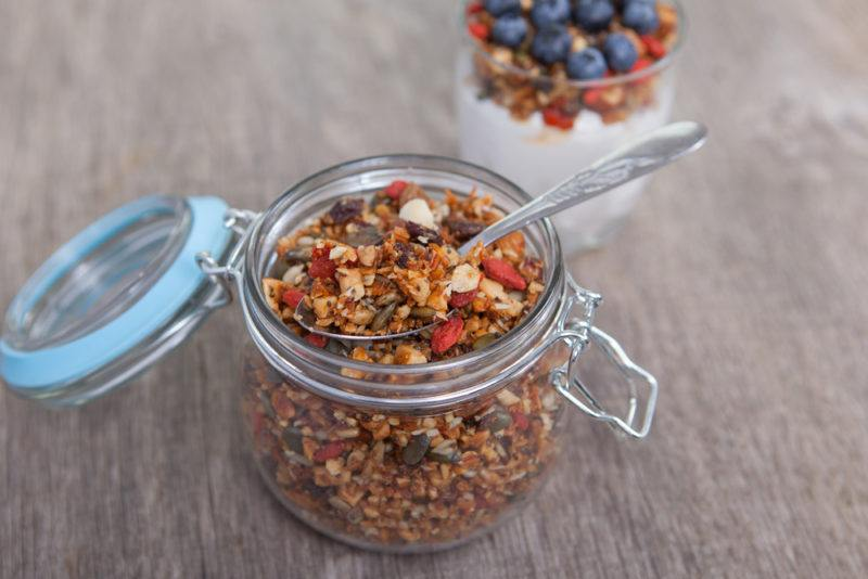 A glass jar with a lid containing homemade granola, with a parfait in the background