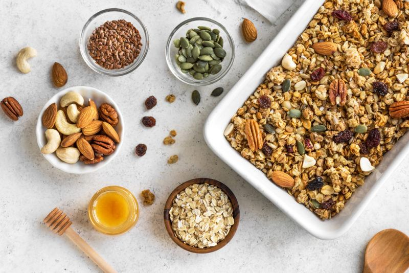 A white pan of granola, with ingredients like seeds and oats on their own in bowls too