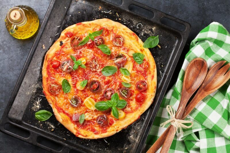 A fresh homemade pizza with red sauce, meat, and greens