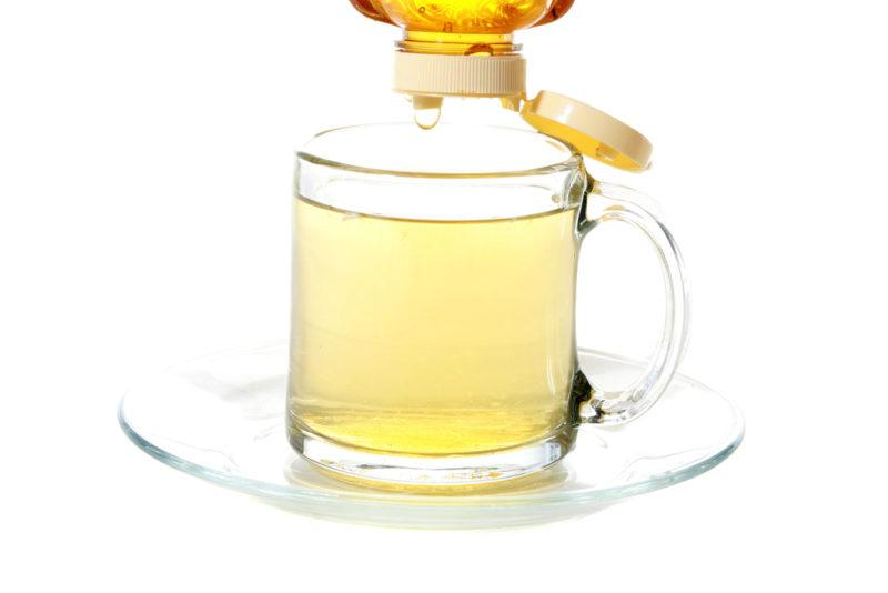 A glass of honey and hot water with honey being dripped into it