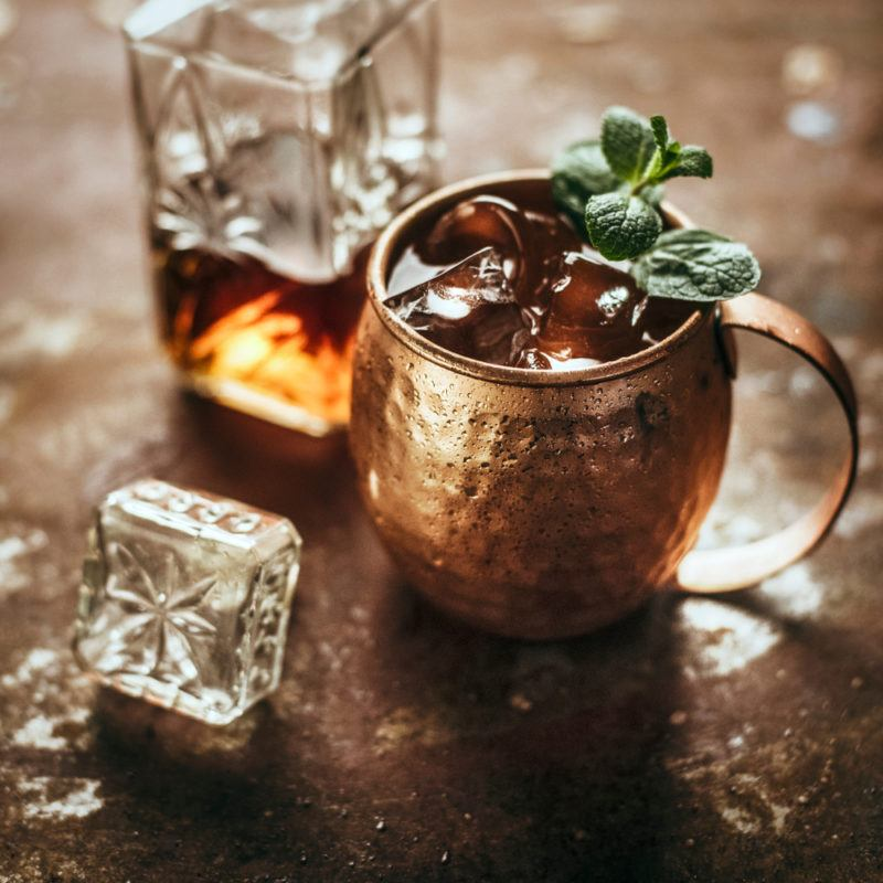 A horsefeather cocktail in a copper mug, with a decanter of whiskey next to it