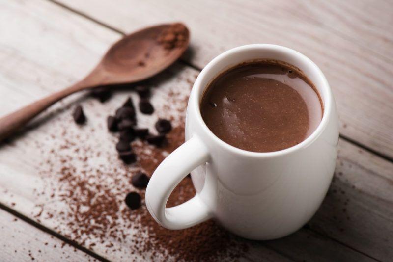 A mug of hot chocolate and a spoon