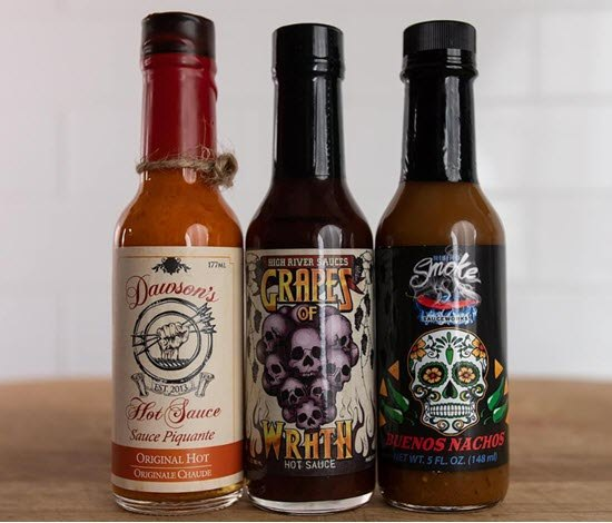3 bottles of hot sauce on a wooden table