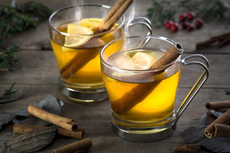 Two hot toddies in glass mugs with cinnamon sticks